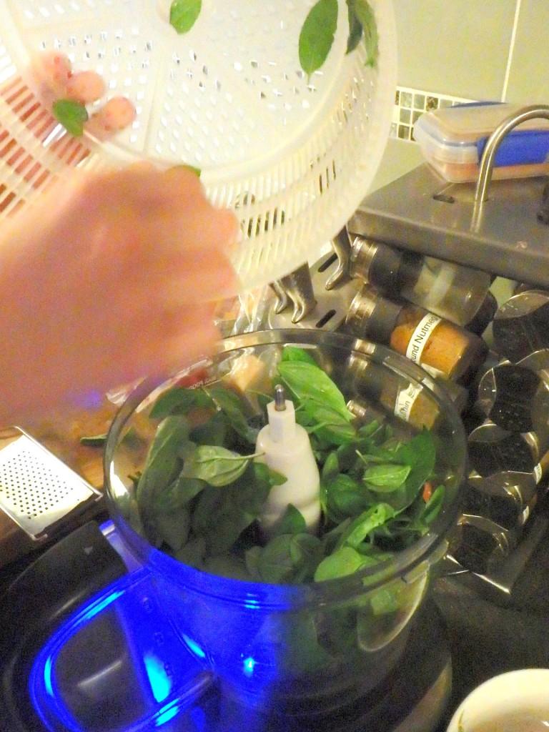 Adding basil leaves to food processor