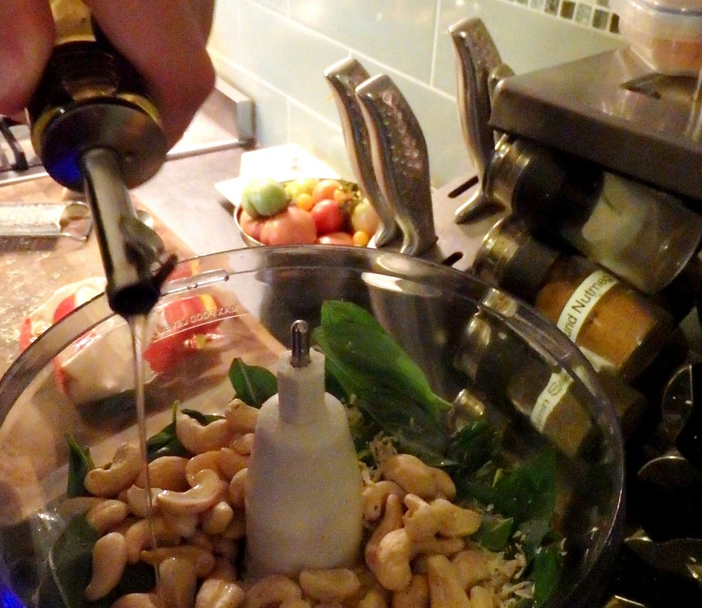 Adding cashew nuts and olive oil to make pesto